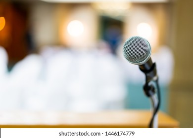 Wired microphone set up on the front of conference room close up with blurred background.  Wired microphone close up with copy space background.