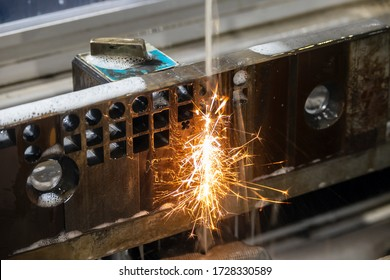The wire-EDM machine cutting the die parts with the sparking light. The mould and die manufacturing process by wirecut machine control by CNC program.