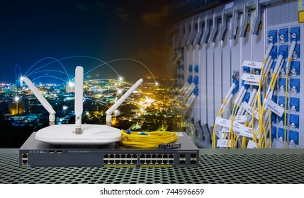 Wireless Access Point with Three external Antenna and Gigabit Network switch and yellow fiber optic cable blending or double exposure with smart city at night for high speed telecommunication.