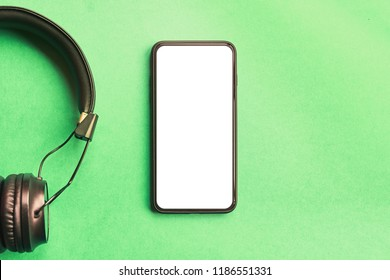 Wireless black headphones for music isolated sound and frameless smartphone on colorful green background. Top view mock-up