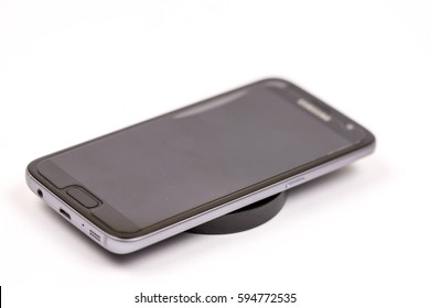 Wireless black mobile charger with mobile phone isolated over white background.