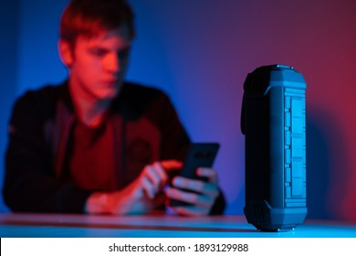 Wireless bluetooth speaker. Column controlled via bluetooth on table. He plays music through his phone. Wireless speaker is controlled by bluetooth technology. Man with phone is blurred in background