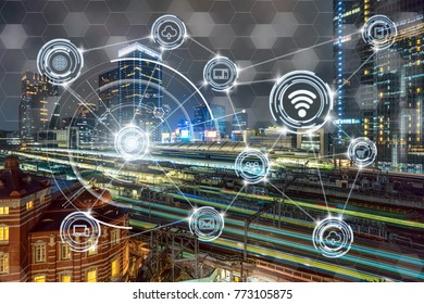Wireless communication connecting of smart city Internet of Things Technology over Train Transportation Scene of Tokyo railway station from terrace at twilight time,business IOT concept.