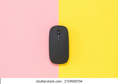 Wireless computer mouse on a yellow and red background.