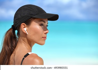 Wireless earbuds running woman on fitness workout. Active lifestyle athlete listening to smartphone music phone app with in-ear gear on beach. Asian woman healthy and active on summer vacation.