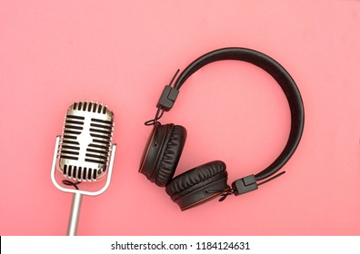 Wireless headphone with microphone on pink background, Music concept.