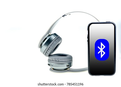 Wireless headphones with moblie phone isolated on a white background,  white headphone, bluetooth
