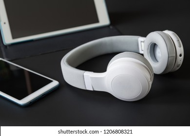 Wireless headphones on the background of a smartphone and tablet. Dark background, closeup, selective focus