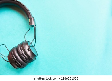 Wireless headphones on colorful blue background. Earphones on azure background for music sound with copyspace for text flatlay