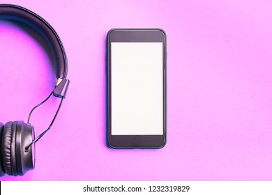 Wireless Headphones and smartphone on colorful background. Flat lay concept: earphones and telephone on pink pastel backdrop