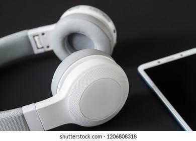 Wireless headphones and smartphone on the dark background. Closeup, selective focus