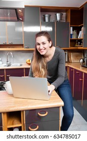 wireless home concept - joyous beautiful young woman standing to work on her laptop set on her kitchen counter for wellbeing, indoors