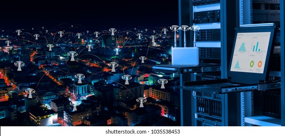 Wireless management center and telecommunication concept, data center with wireless access point device, kvm monitor and servers on rack and background of night city with wifi icon connectivity