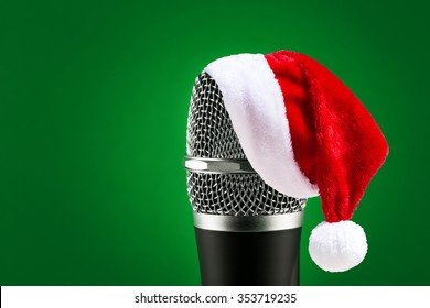 Wireless microphone with santa hat on it closeup on green background