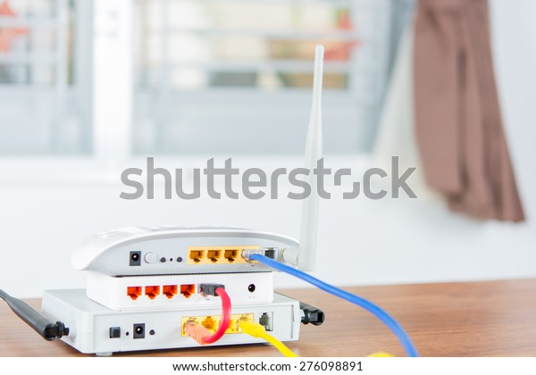 Wireless modem router network hub with cable connect on wooden table in the room