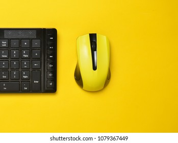 Wireless mouse and keyboard isolated on yellow pastel background. Top view, minimalist trend