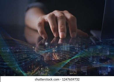 Wireless network communication, Internet of Things IoT concept. Double exposure, business man, programmer working on laptop computer and smart city with technology effect on virtual screen, dark tone