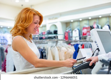 Wireless payment using smartphone and NFC technology. Close up. Female customer paying with smart phone in shop. Close Up shopping