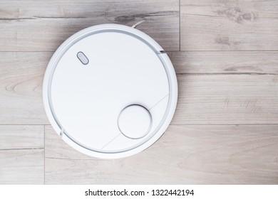 Wireless robot vacuum cleaner on the floor top view. Smart household technologies.