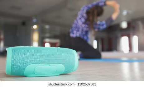 Wireless speaker in front of young woman stretching on the rug
