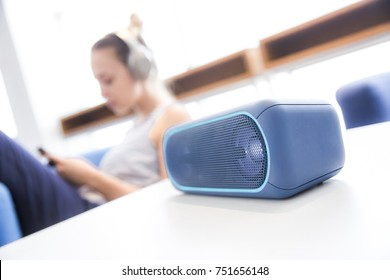 Wireless speaker with girl with headphones in a background
