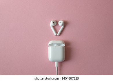 wireless white headphones on pink background. Airpods. wireless white headphones with charger connected. Copy space