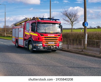 Wirral, UK - Mar 13 2021: A red Scania fire engine on an urban road in the UK, taken in winter.