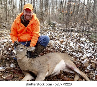 Wisconsin deer hunter with a spike buck in the woods