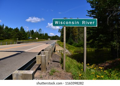 The Wisconsin River sign at the headwaters near Land O Lakes, Wisconsin with a bright clouded blue sky.