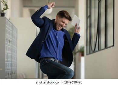 Wish come true. Euphoric happy male executive employee manager worker jumping dancing at office hallway screaming in delight getting career salary growth, finding hard solution, receiving job of dream