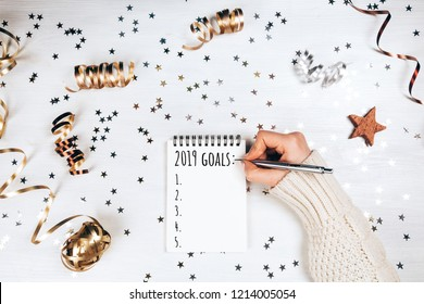 Wish lift for New Year. Holiday decorations and notebook with wish list on white rustic table, flat lay style. Planning concept.