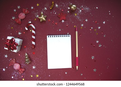 Wish list for New Year. Notebook and glittering Christmas decorations on red background. Flat lay style. Planning concept.