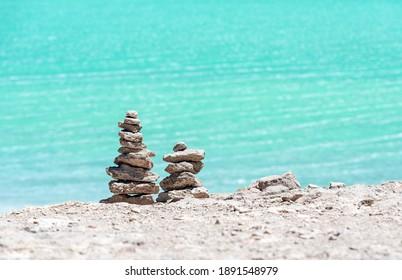 Wish pyramids in front of the Laguna Verde (Green Lagoon), Uyuni, Bolivia.