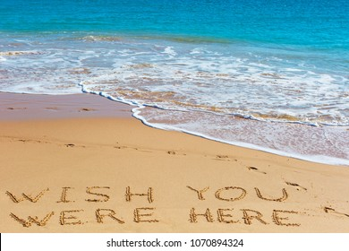 WISH YOU WERE HERE insctiption on wet beach sand with the turquoise sea on background. Summer season  vacation concept.