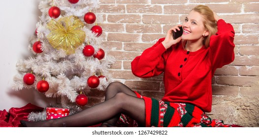 Wishing everyone merry christmas. Waiting for christmas. Voicemail greeting. Woman cheerful hold smartphone enjoy mobile phone conversation. Girl in dress sit near christmas tree with ornaments.