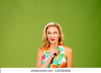 Wishing for....Portrait of a beautiful blonde woman with finger under chin, isolated on green studio background