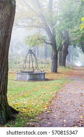 A wishing well in a park on a foggy fall morning.