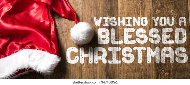 Wishing You a Blessed Christmas written on wooden with Santa Hat