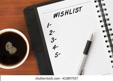 Wishlist word on a notebook with a pen and a cup of coffee