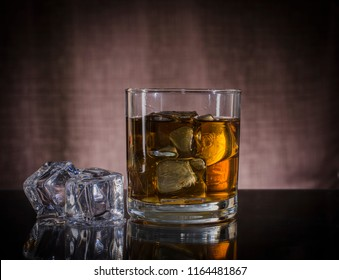 wisky on the rock in a glass on table and Brown background.