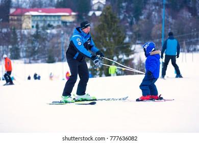 Wisla, Poland, 18.02.2016 - man teaching little kid how to ski holding two sticks