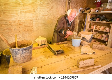 WISMAR, DE - SEPTEMBER 14, 2017: Craftsman shows how to work with clay making bricks using old construction techniques in Saint Mary s Church in Wismar, Mecklenburg-Vorpommern state, northern Germany.