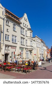 WISMAR, GERMANY - APRIL 19, 2019: People enjoying the sun at the market square of Wismar, Germany