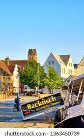 Wismar, Germany - May 13, 2018: Fishing boat in the old harbor of Wismar. Letters with Backfisch, Fischbrötchen, Pommes means fried fish, fish rolls, French fries.