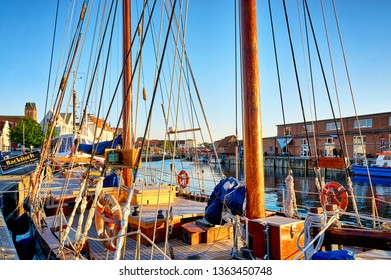 Wismar, Germany - May 13, 2018: Sailboat in the old harbor of Wismar. Letters with Backfisch, Fischbrötchen, Pommes means fried fish, fish rolls, French fries.