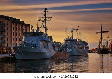 Wismar, Germany - October 07, 2018: Military boats in the harbor of Wismar with sunset over the Baltic Sea in the background.