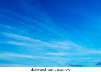 Wispy blue sky with white airy clouds background. Abstract nature texture wallpaper of beautiful sunny cloudy sky in summer or spring morning sunlight at daylight horizon, panoramic view, copy space