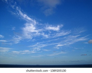 WISPY CLOUDS IN BLUE SKY ABOVE OCEAN