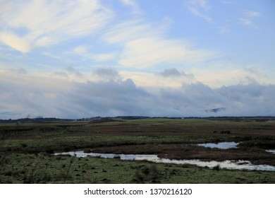 Wispy clouds over a barren landscape, stream foreground. Fife, Scotland.