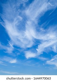 Wispy white cloud formation against a vibrant blue sky